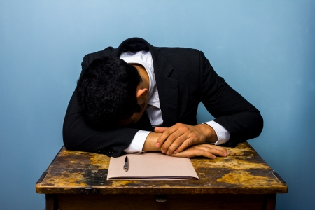 businessman is asleep at an old desk photo