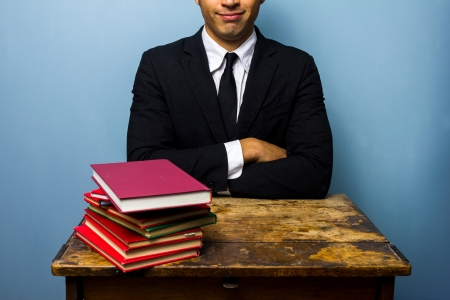 businessman at an old desk with a stack of books photo