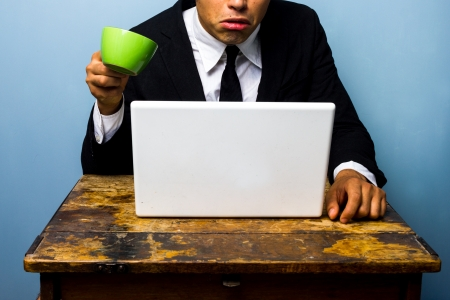 startled: Shocked businessman nearly spilling coffee on his laptop computer
