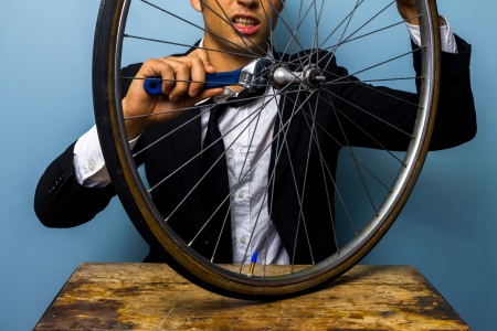 Young businessman is trying to fix a bicycle tyre photo
