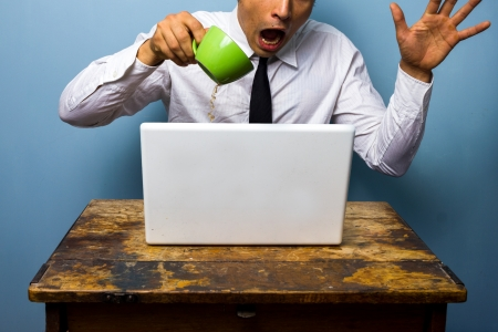 Clumsy businessman spilling coffee on his laptop photo