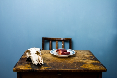 satanism: Goat s skull and raw heart on table