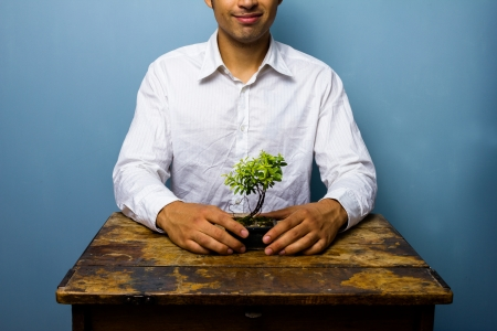 Man is caring for his little bonsai tree photo