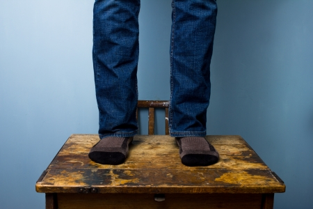 Man in socks standing on an old desk photo