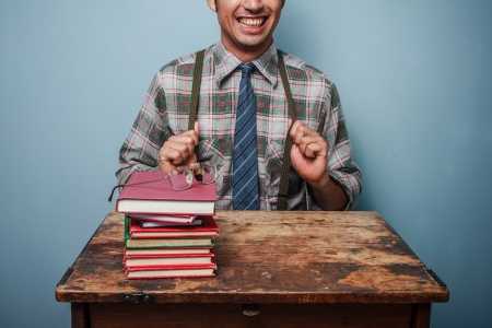 Geek is showing off his braces and looking at books Stock Photo - 21562031