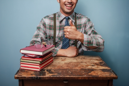 Happy geek man is giving thumbs up at books Stock Photo - 21562032