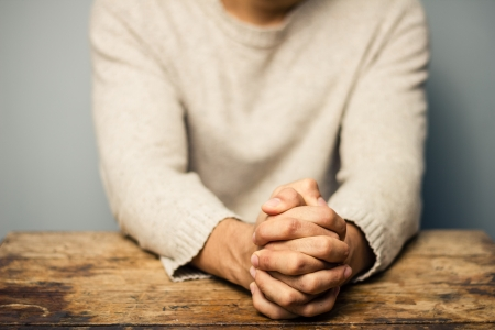 unrecognisable people: Praying man at old desk