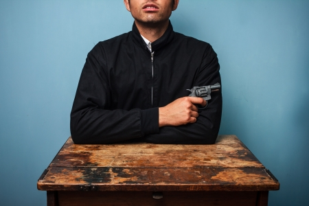 Thug at table with a gun in his hand photo