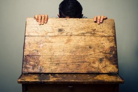 old desk: Man looking inside old school desk