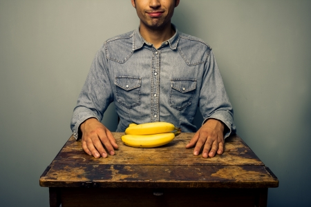 preperation: Happy man at desk with a bunch of bananas Stock Photo
