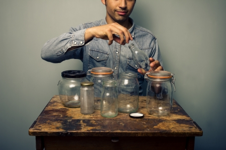 preperation: Man sitting at old desk with empty jars in front of him