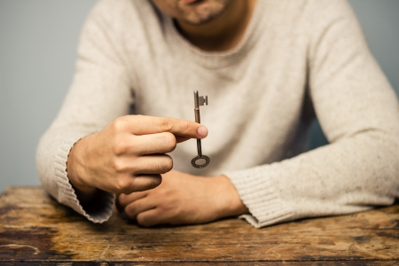 escape key: Man at desk is holding a key Stock Photo