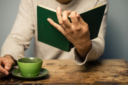 unrecognisable people: Man at table drinking coffee and reading