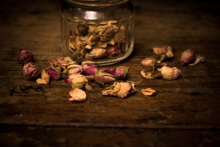 Romantic scene of dried rose petals on rustic woo surface photo