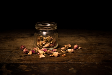 to woo: Romantic scene of dried rose petals on rustic woo surface