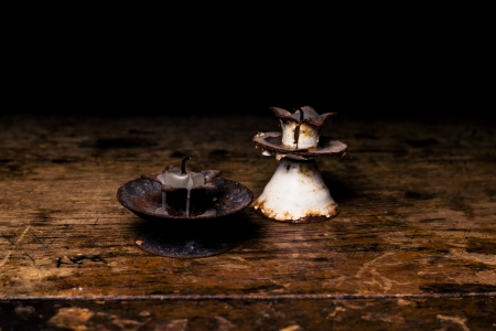 burned out: Rusty old candle sticks on wood surface