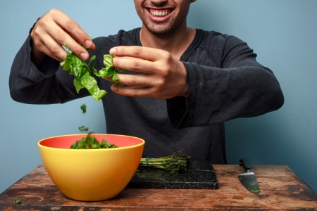 Man making a salad with his hands at table