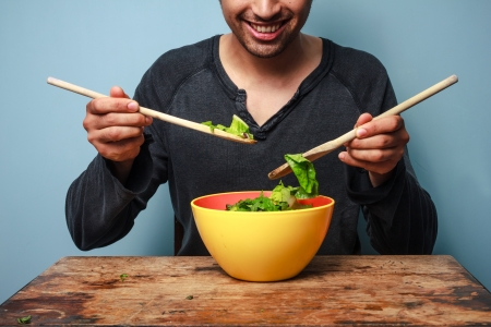 preperation: Man tossing salad with wooden spoons at table