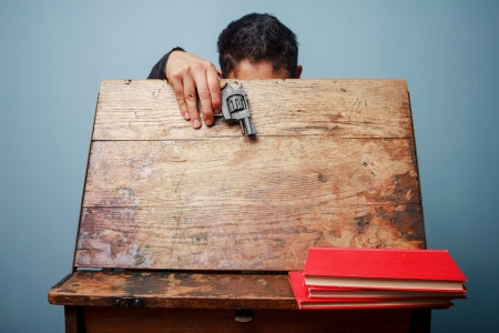 Student with a gun looking inside an old school desk
