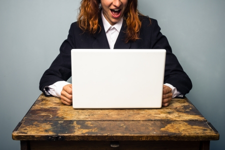 Business woman excited about news on her laptop photo