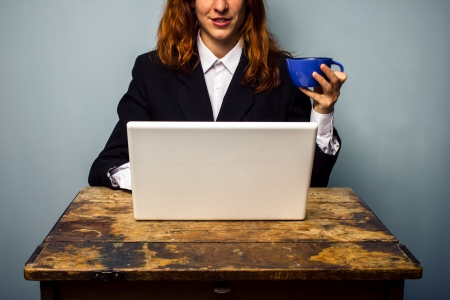 Business woman with laptop drinking coffee photo