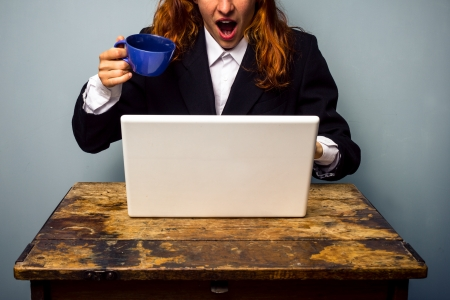 Woman almost spilling coffee on her laptop after seeing stratling news photo