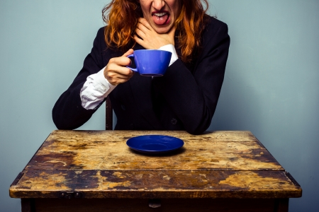 unrecognisable people: Woman has had a very bad tasting cup of coffee