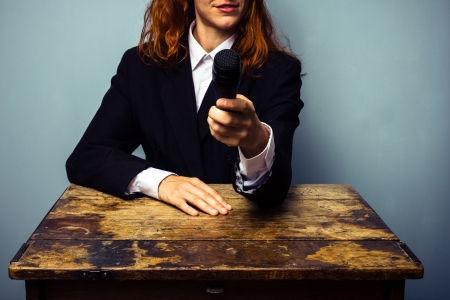 unrecognisable people: Business woman pointing microphone at camera