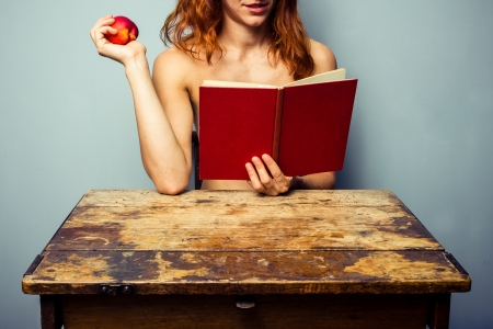 nude woman sitting: Naked woman reading a book and eating a peach