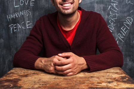 uplifting: Smiling man in front of blackboard with uplifting words