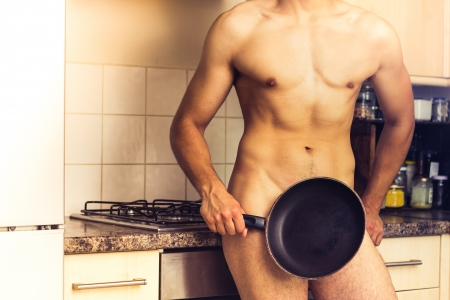 Naked man is standing by cooker with a frying pan Stock Photo