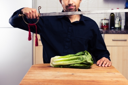 Silly man cutting lettuce with a sword