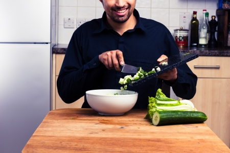 preperation: Young man is making a salad in his kitchen  Stock Photo