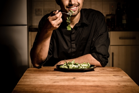 Young man is having dinner by himself in his kitchen photo