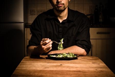 젊은 남자가 그의 부엌에서 자신이 저녁 식사를한다