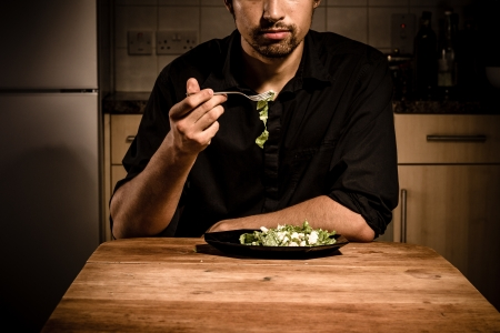 unmarried: Young man is having dinner by himself in his kitchen