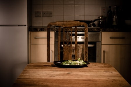 Plate of food on table in kitchen at night photo