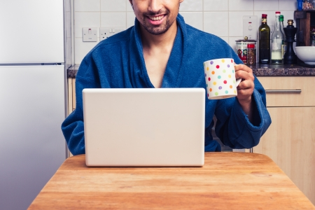 Happy man drinking coffee in his kitchen and working on laptop photo