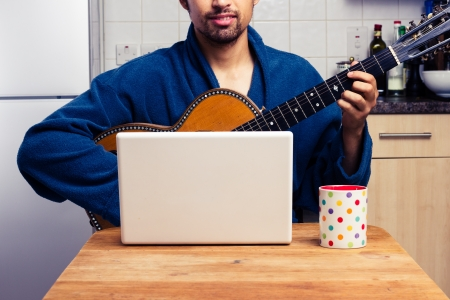 man playing guitar: Man in robe is teaching himself to play guitar at home