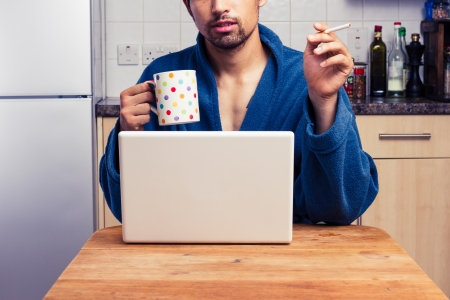 Man in robe is working on laptop and drinking coffee and smoking photo