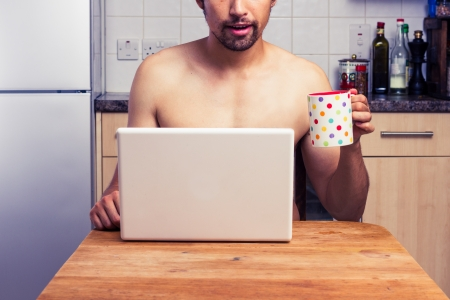 Naked man is drinking coffee and working on laptop