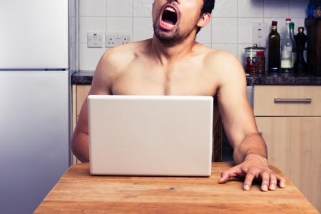 uomo nudo: Giovane nudo sta guardando la pornografia sul suo computer portatile