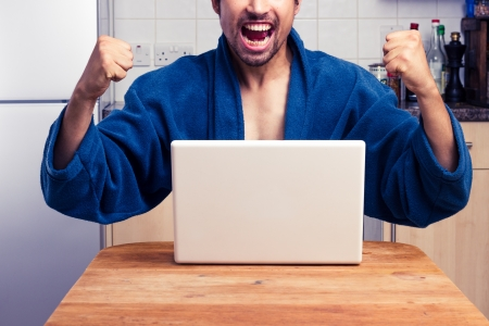 Happy man is very excited about something on his laptop photo