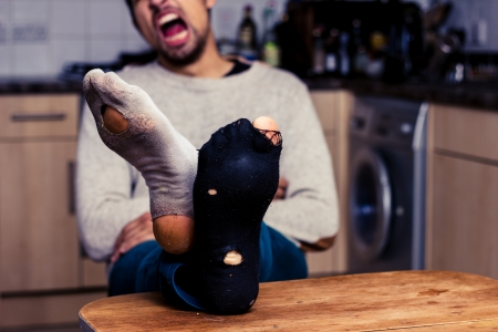 Tired man with worn out socks sitting at table in kitchen
