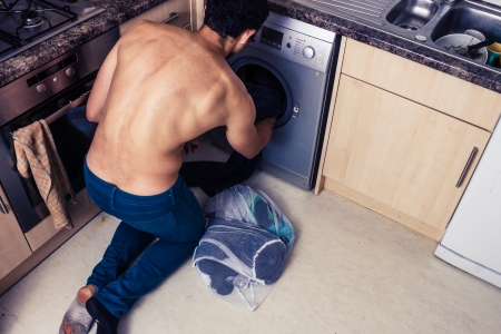 Young man is loading up his washing machine photo