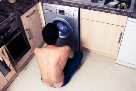 Young man is in his kitchen watching his washing machine photo