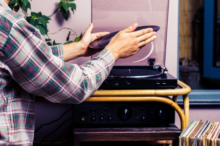 Hands placing LP record on a turntable photo