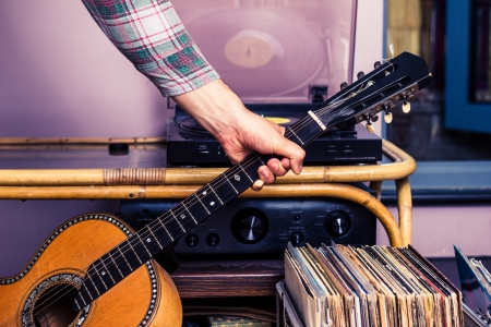 Man picking up guitar after listening to records photo