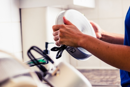 Woman doing the washing up in kitchen Stock Photo - 21923898