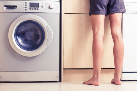 unrecognisable: Woman s bare legs in kitchen by washing machine